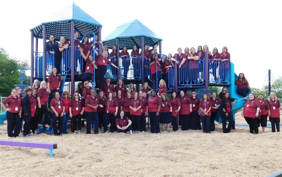 Photo of the entire JSE staff outsie on the playground equipment